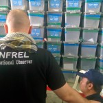 ANFREL observers look on before stacks of already audited boxes